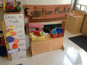 Children help transform the classroom into an Egyptian market.